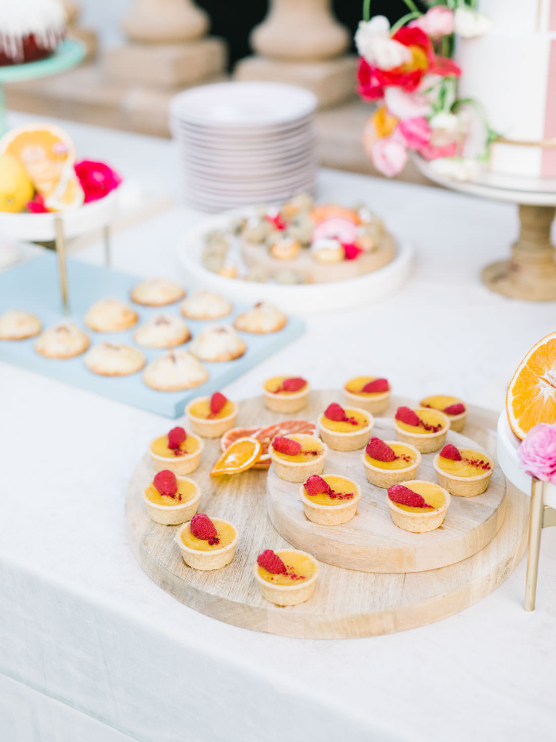 Mini Passion fruit tarts on a wooden serving board on top of velvet linen