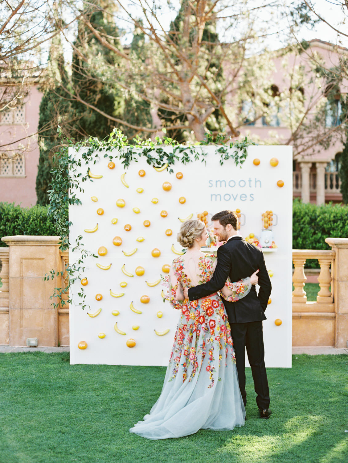 "Bride in colorful Marchesa gown with groom admiring outdoor escort display with text ""smooth moves"" and smilax framing top and side. Escort cards made from faux fruit bananas and oranges with guest names in white ink. Three colorful Smeg blenders on a shelf filled with fruit. A Wedding Photographer's Fairmont Grand Del Mar Wedding"