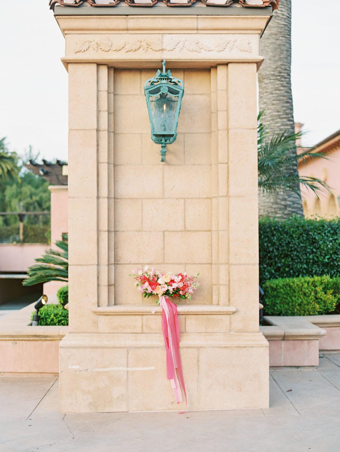 Large bridal bouquet with pink, fuschia, peach, ivory, and blush flowers and long pink ribbons resting on a column.