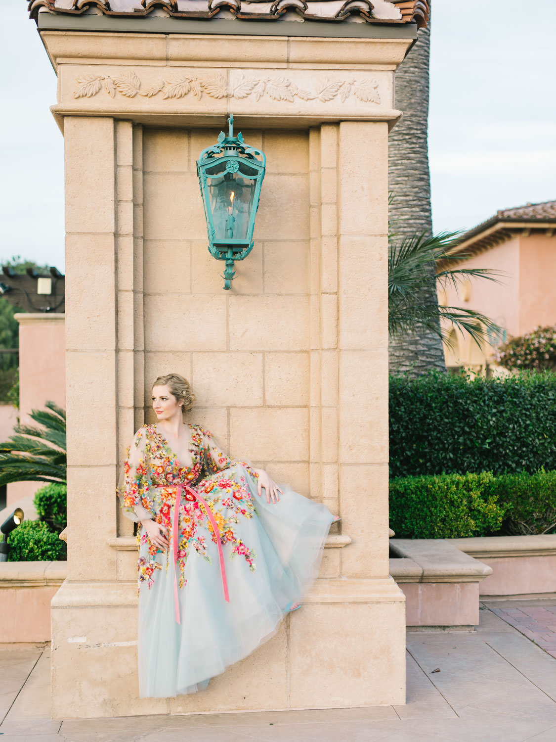 Bride wearing colorful Marchesa wedding gown with blue, pink, yellow, green, and orange floral appliques. Marchesa Resort 2018 long sleeve gown.