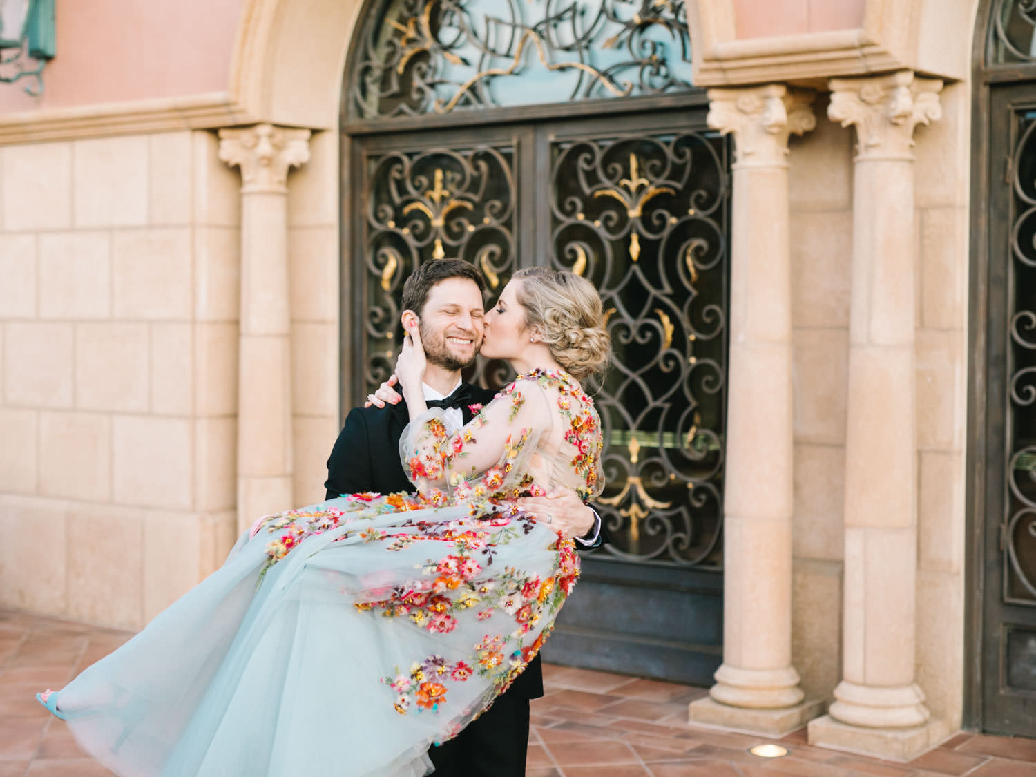 Bride wearing colorful Marchesa wedding gown with blue, pink, yellow, green, and orange floral appliques. Groom picking up bride.