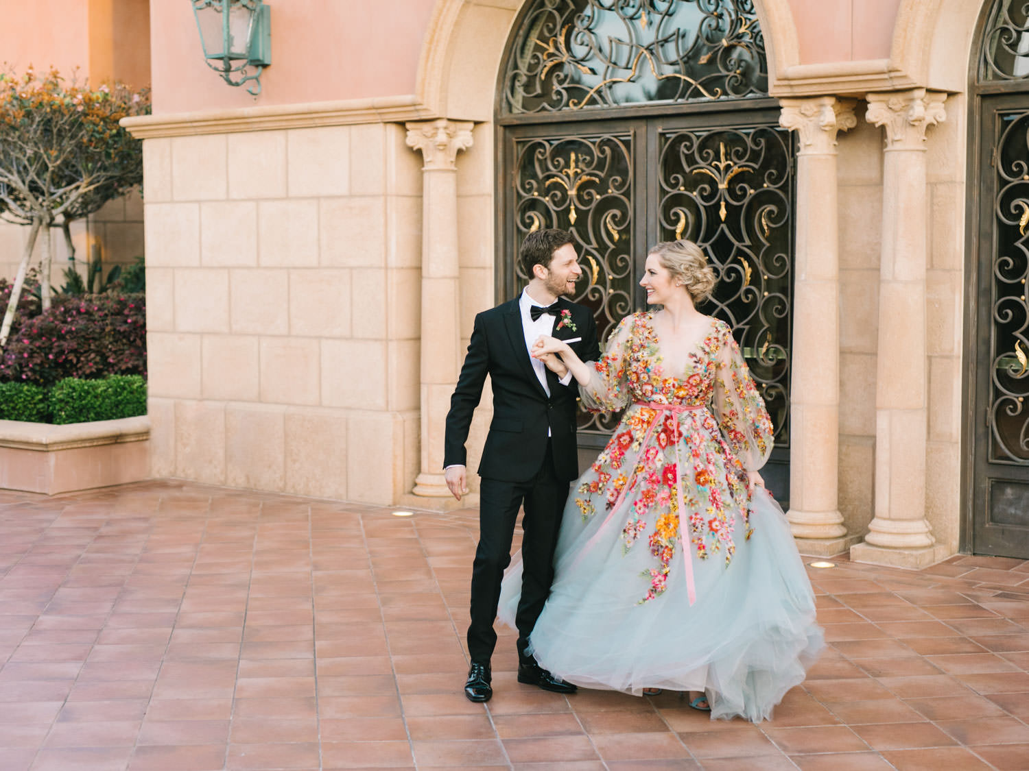 Bride wearing colorful Marchesa wedding gown with blue, pink, yellow, green, and orange floral appliques. Groom walking with bride.