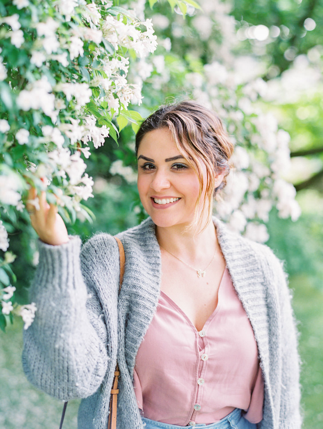 Barnsley House Hotel woman in grey sweater and pink shirt in a flower bush. Flutter Magazine Retreat in the Cotswolds, England. Photo by Cavin Elizabeth Photography on film