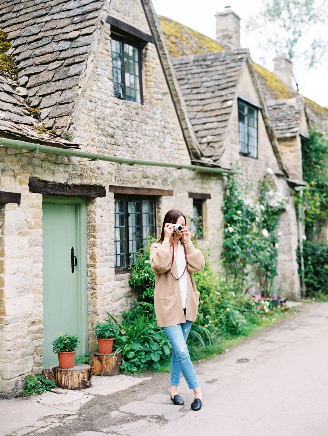 Woman in beige sweater and jeans taking a photo. Bibury village house with in the Cotswolds. Flutter Magazine Retreat in the Cotswolds, England. Photo by Cavin Elizabeth Photography on film