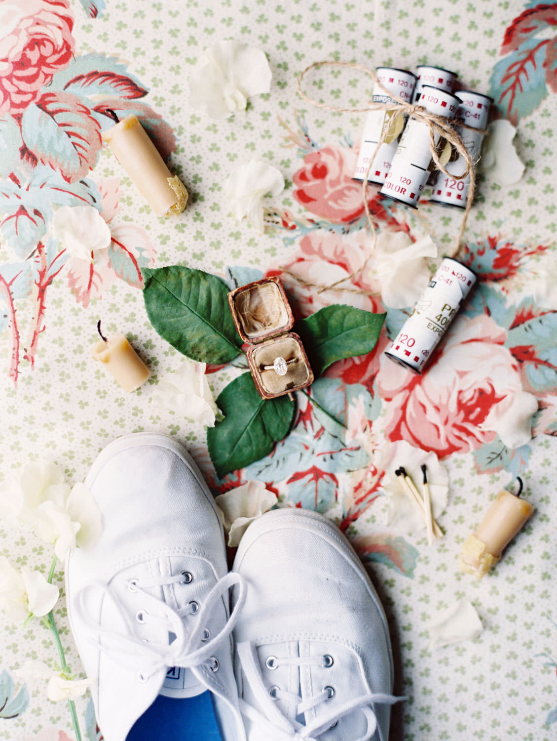 Flatlay on film of white Keds sneakers, Fuji 400h film, candles and matches, and engagement ring in a vintage ring box by Cavin Elizabeth Photography