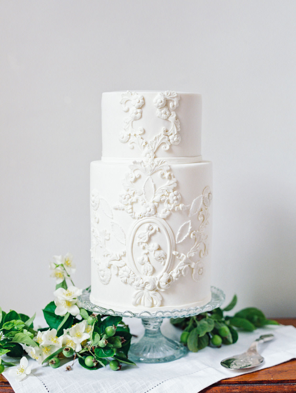 MonAnnie Cakes two tier white cake with intricate sculpture like design inspired by an English ceiling. Elegant fine art cake styled by Joy Proctor and photographed on film by Cavin Elizabeth Photography