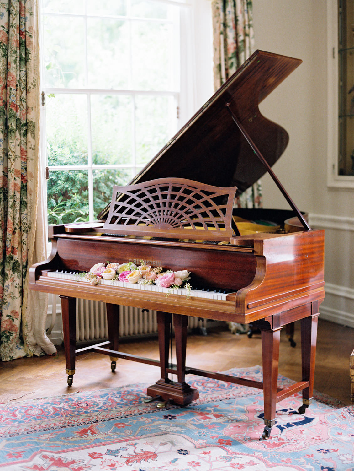 Piano styled with roses on the keys by Social and Co Events photographed by Cavin Elizabeth Photography on film