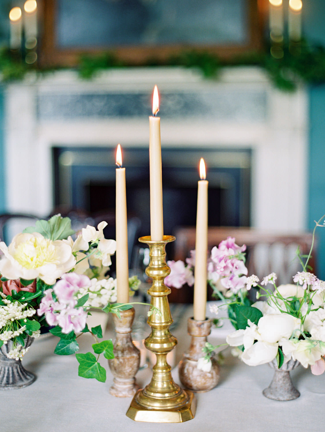 Dinner tablescape styled by Joy Proctor and Bows and Arrows Flowers. Blue chinoiserie tea cups, grey linen, taupe tall candles, and centerpieces with mauve, ivory, yellow, and green. Flutter Magazine Retreat in the Cotswolds at Norton Hall in Mickleton, England. Photo by Cavin Elizabeth Photography on film