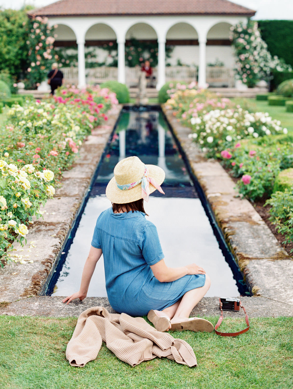 Woman sitting by the fountain at Renaissance garden at David Austin Roses in England. Film by Cavin Elizabeth on the Flutter Mag Retreat