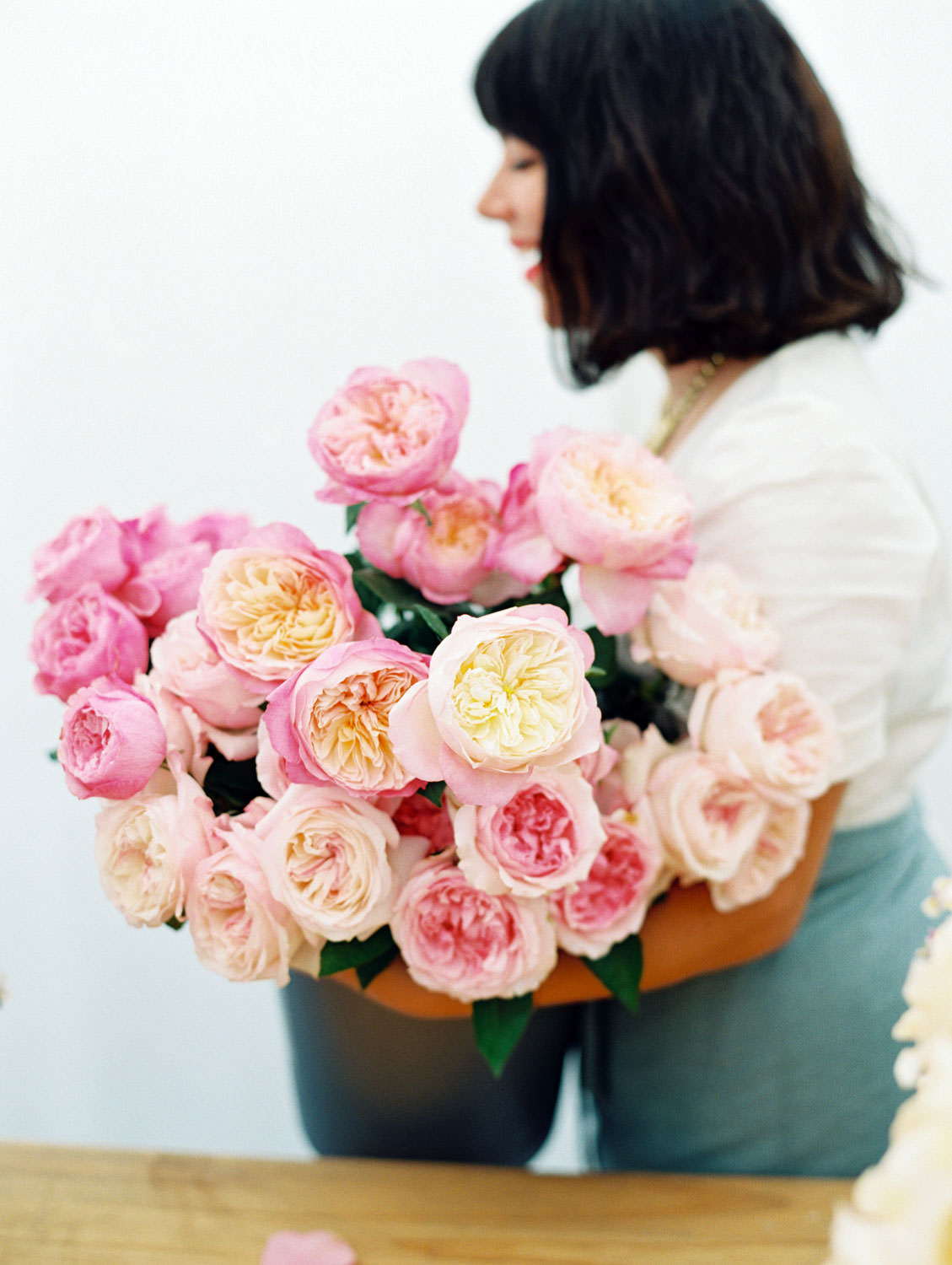 Bucket of David Austin pink roses. Centerpiece flower arranging workshop by Bows and Arrows flowers on the Flutter Magazine Retreat in the Cotswolds. Film by Cavin Elizabeth Photography
