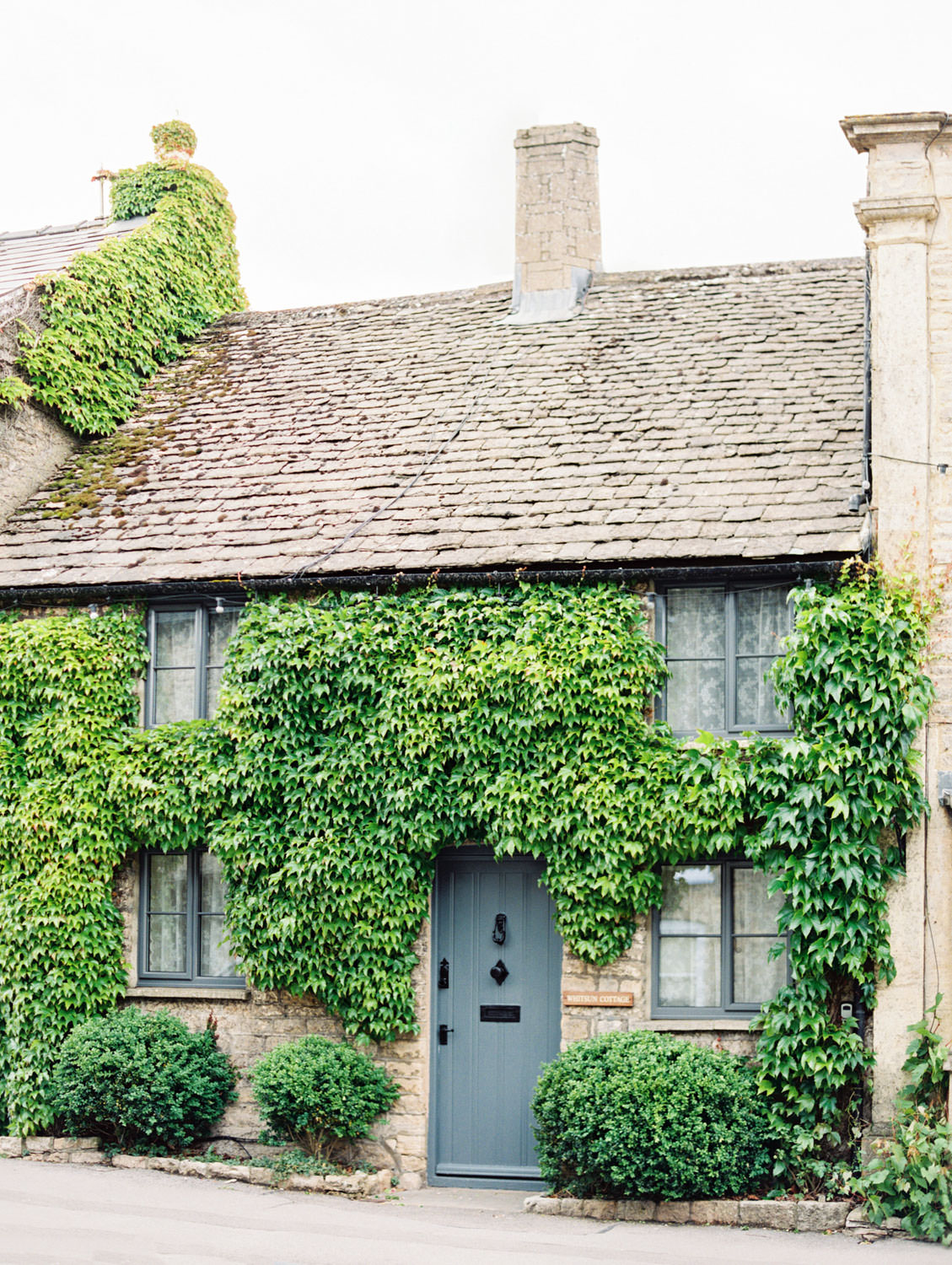 Stow-on-the-Wold village house with ivy and French blue door in the Cotswolds. Flutter Magazine Retreat in the Cotswolds, England. Photo by Cavin Elizabeth Photography on film