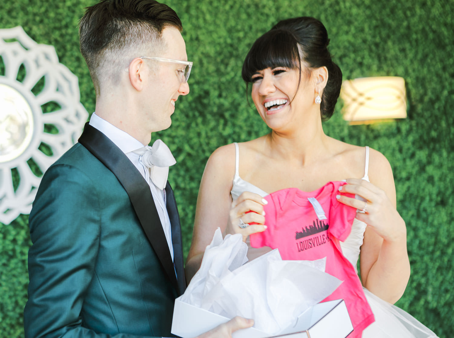 Groom in dark teal tuxedo opening a gender reveal gift during the first look with bride in beehive updo wearing a Matthew Christopher gown. Cavin Elizabeth Photography