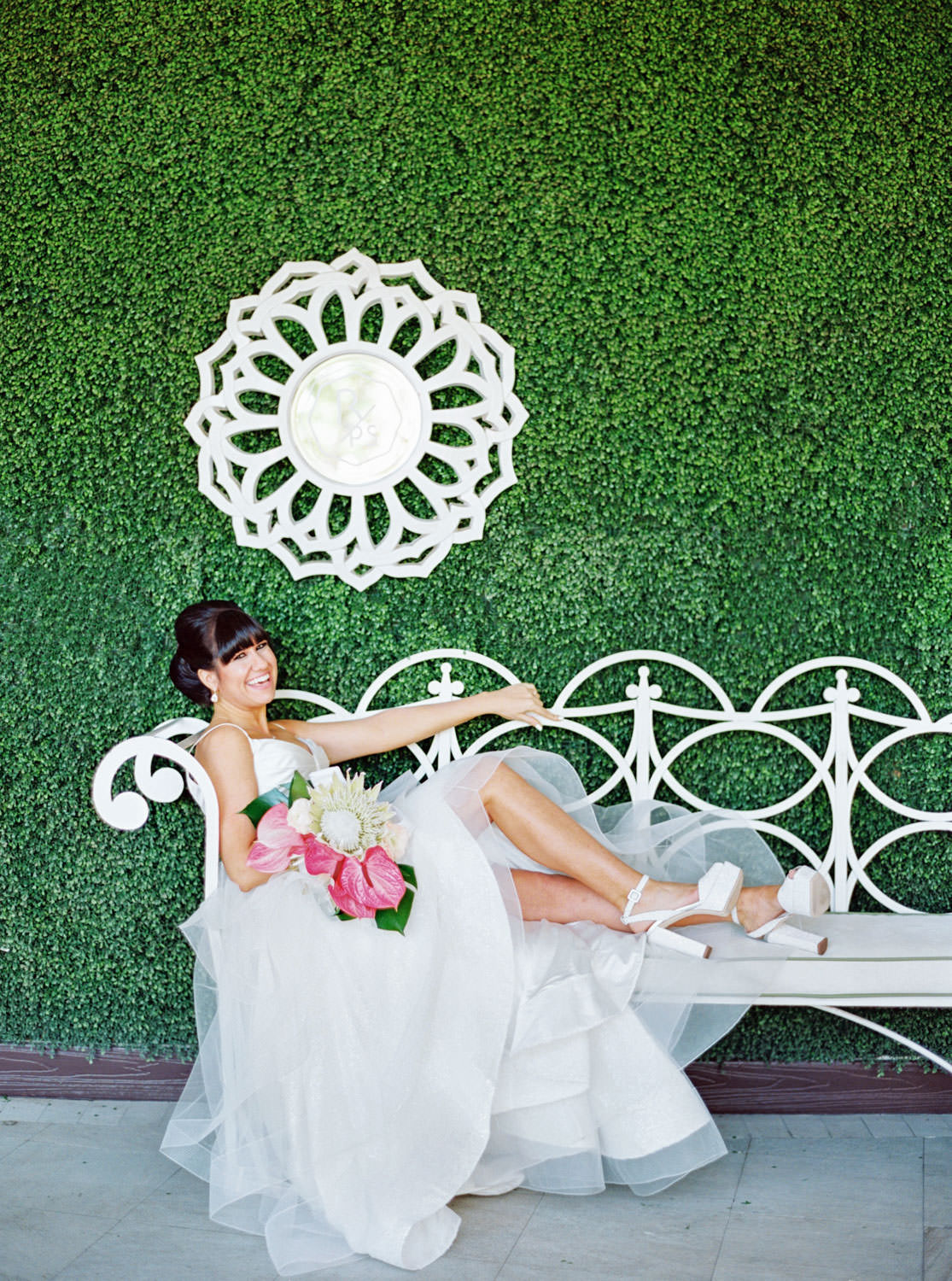 Bride in beehive updo wearing a Matthew Christopher gown lounging on a sofa outdoors in front of a greenery wall. Bridal bouquet with protea, pink anthurium, and palm leaves. Cavin Elizabeth Photography