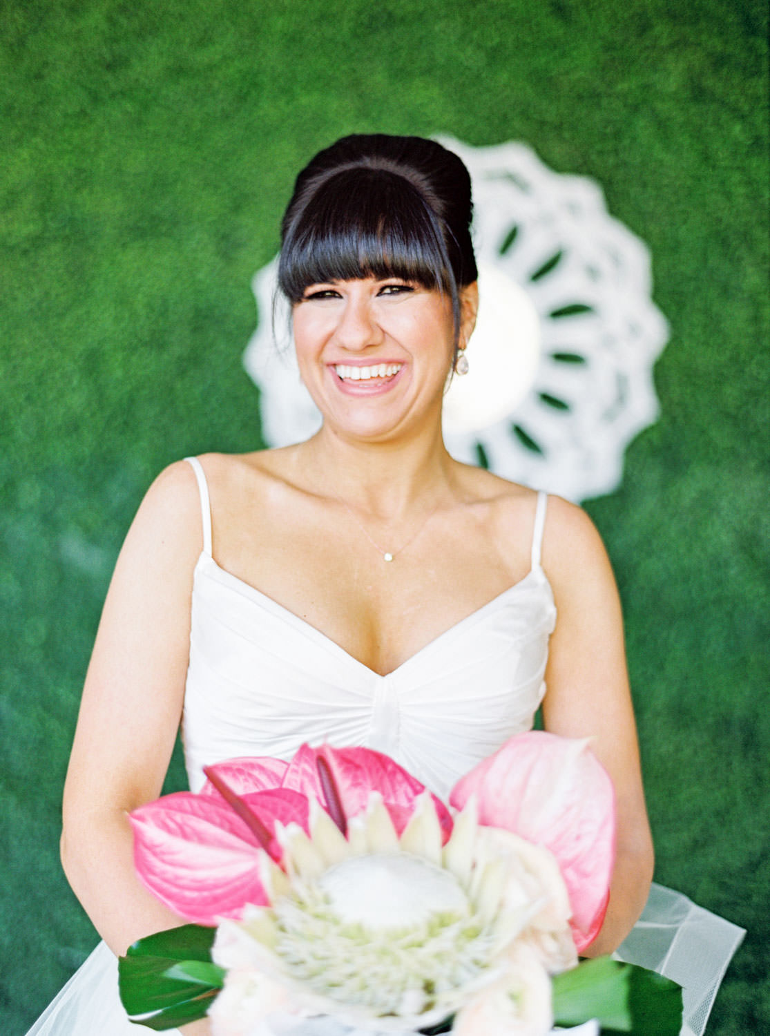 Bride in beehive updo wearing a Matthew Christopher gown in front of a greenery wall. Bridal bouquet with protea, pink anthurium, and palm leaves. Cavin Elizabeth Photography