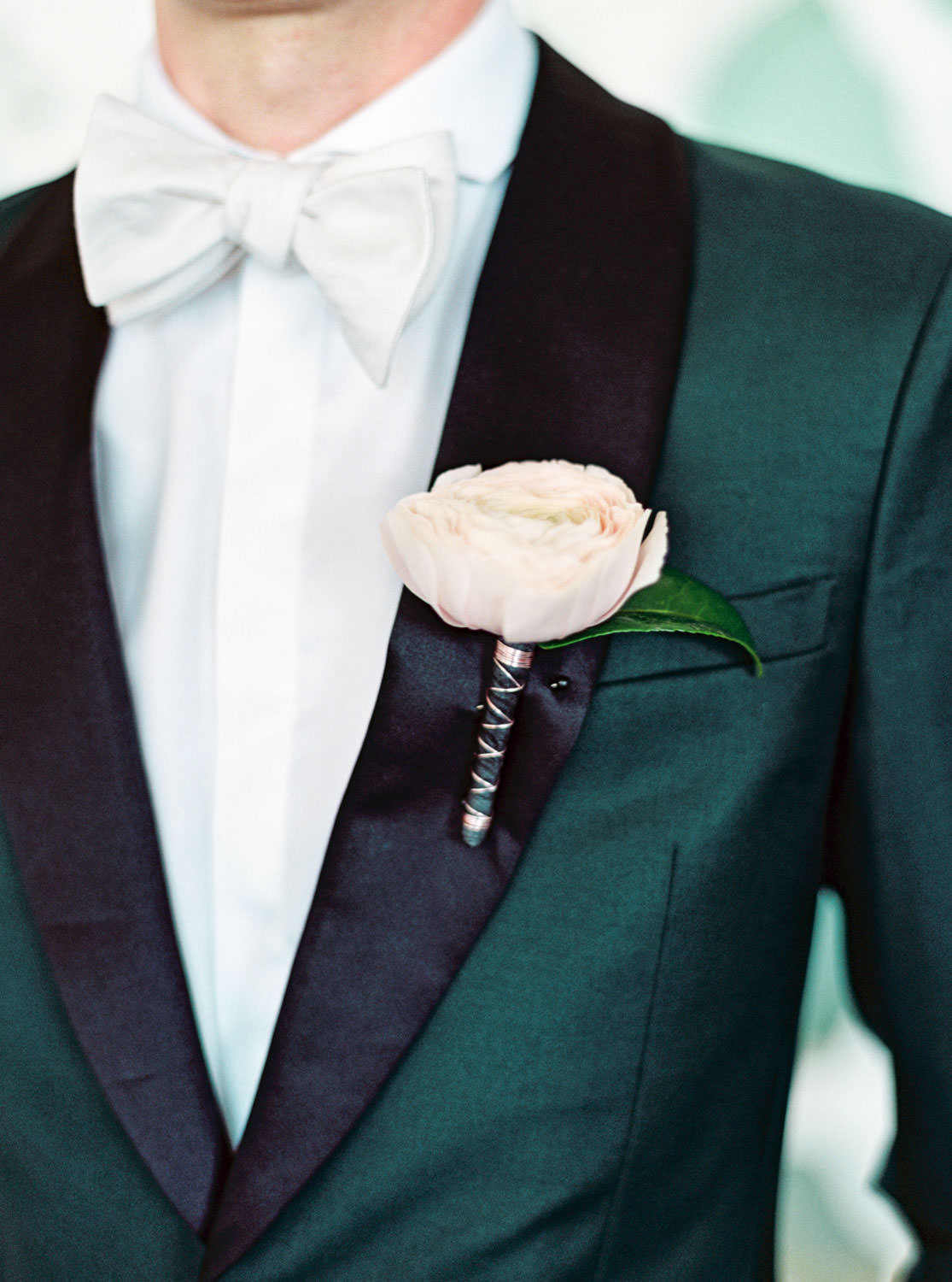 Groom in dark teal tuxedo with black lapel with large blush flower boutonniere and ivory bowtie. Cavin Elizabeth Photography