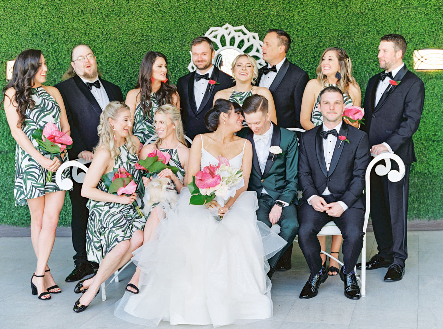 Groom in dark teal tuxedo and groomsmen in black tuxedos. Bridesmaids in tropical palm leaf print short dresses carrying bouquets with palm leaves and pink anthurium. Ceremony white pergola site with large white planters filled with palm leaves and paddle cactus plants covered in blush and fuchsia pink flowers. Riviera Palm Springs Wedding by Cavin Elizabeth Photography