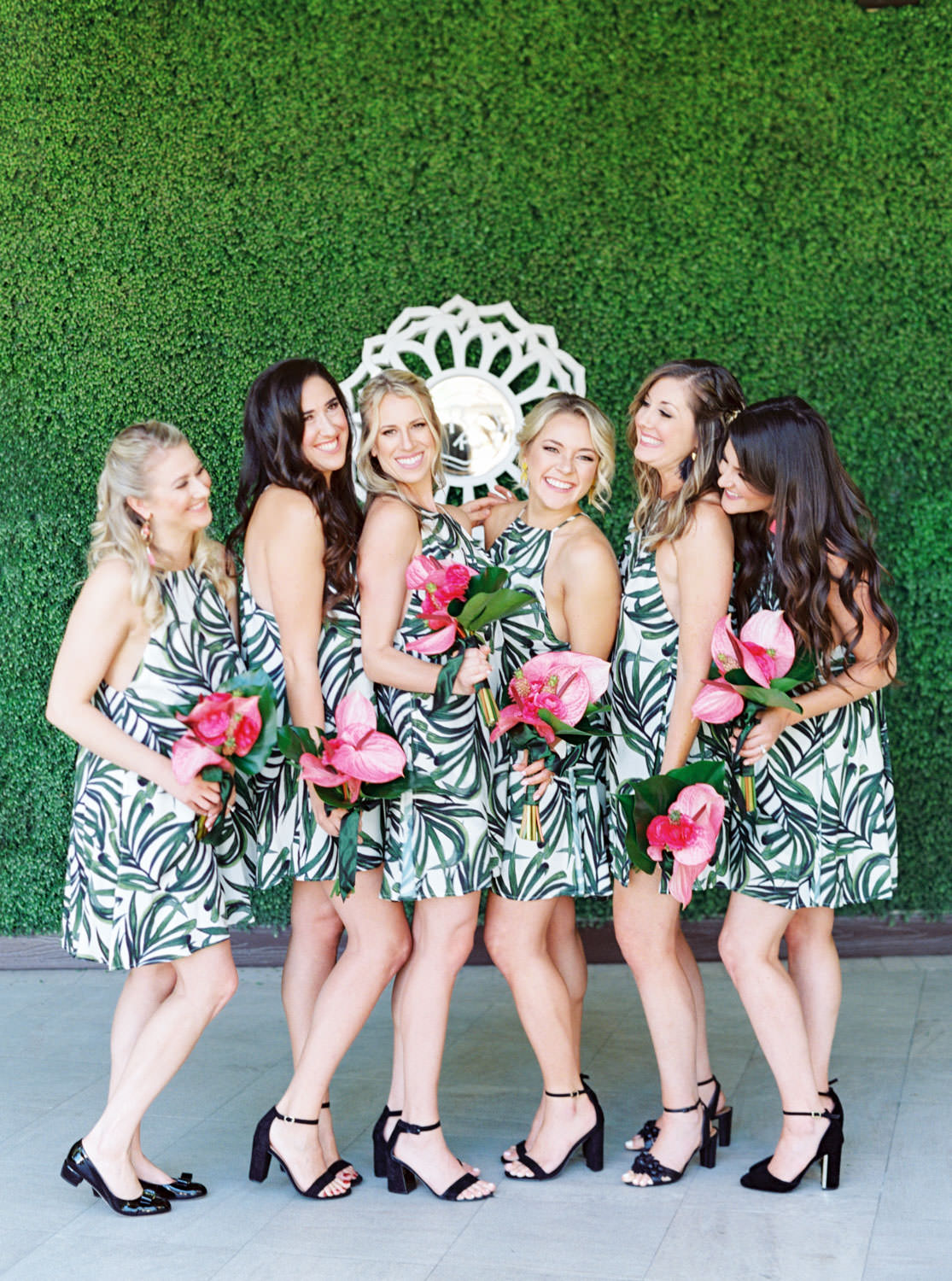 Bridesmaids in tropical palm leaf print short dresses carrying bouquets with palm leaves and pink anthurium. Ceremony white pergola site with large white planters filled with palm leaves and paddle cactus plants covered in blush and fuchsia pink flowers. Riviera Palm Springs Wedding by Cavin Elizabeth Photography