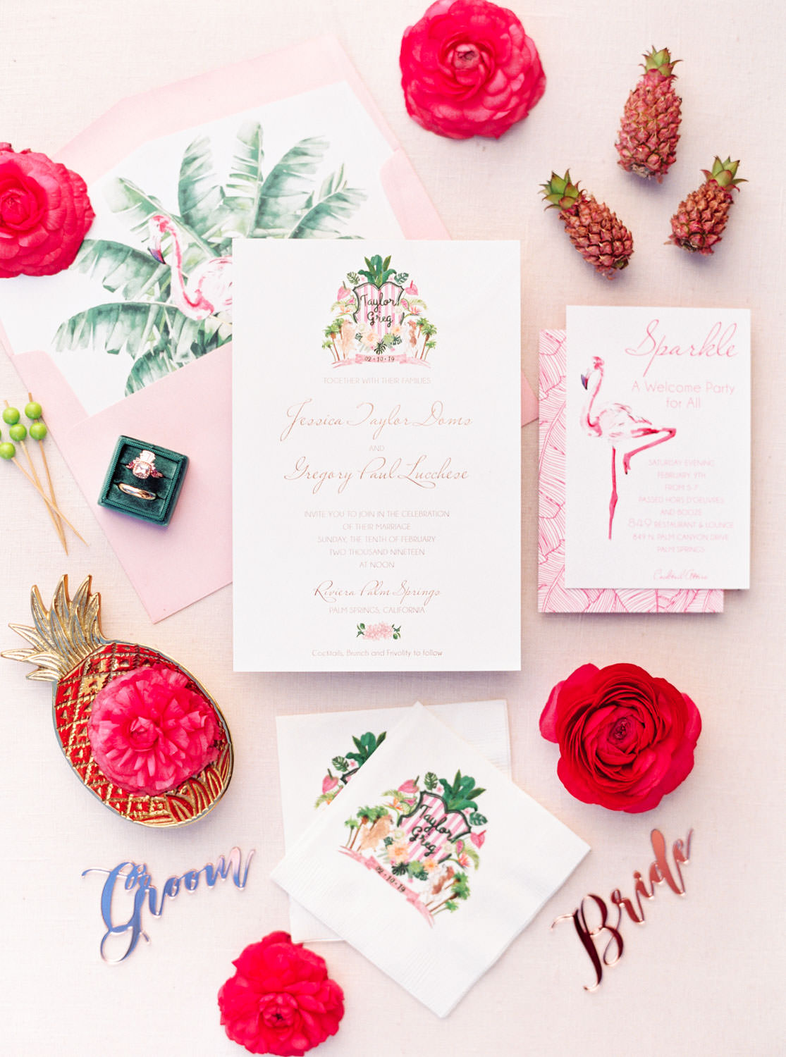 Custom Palm Springs wedding crest on ivory invitation with rose gold text. Pink envelope with palm leaf and flamingo liner. Information card with pink flamingo watercolor, custom wedding crest napkins, mini pineapples and fuchsia flowers styled with laser cut bride and groom place setting cards. Cavin Elizabeth Photography