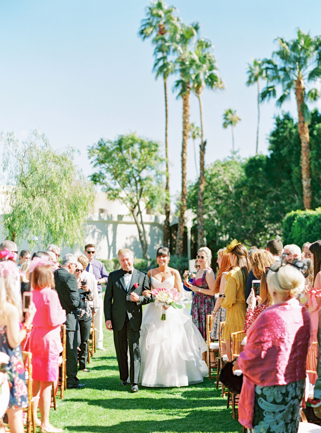 Bride in a Matthew Christopher gown walking down the aisle with her uncle. Riviera Palm Springs Wedding by Cavin Elizabeth Photography