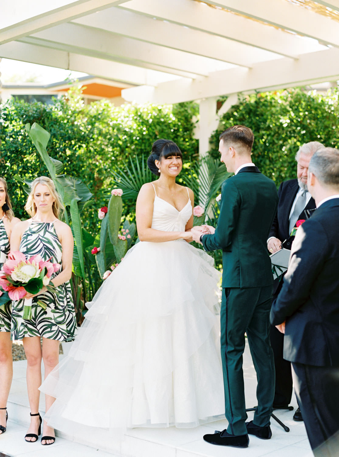 Bride in Matthew Christopher gown with beehive updo and groom in dark teal tuxedo. Bridesmaids in tropical palm leaf print short dresses carrying bouquets with palm leaves and pink anthurium. Ceremony white pergola site with large white planters filled with palm leaves and paddle cactus plants covered in blush and fuchsia pink flowers. Riviera Palm Springs Wedding by Cavin Elizabeth Photography