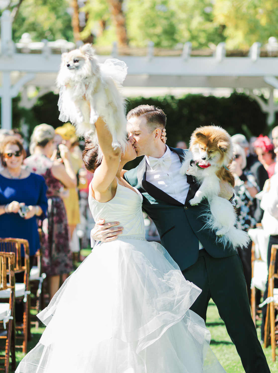 Bride and groom carrying Pomeranians down the ceremony aisle and bride thrusts dog in the air. Riviera Palm Springs Wedding by Cavin Elizabeth Photography