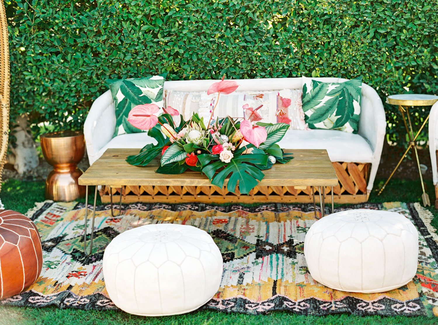 Tropical wedding lounge with boho vibes. White sofa and white tuft seating and palm leaf arrangement on wooden table. Riviera Palm Springs Wedding by Cavin Elizabeth Photography