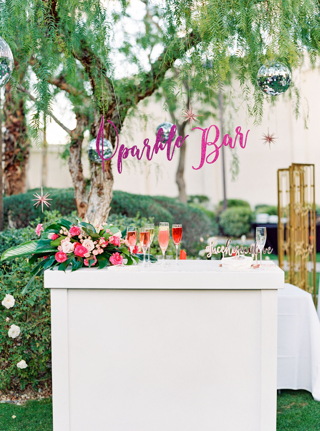 """Hanging purple glitter laser cut bar sign """"Sparkle Bar"""" for a champagne and mimosa wedding bar surrounded by flowers and hanging disco balls. Riviera Palm Springs Wedding by Cavin Elizabeth Photography"""