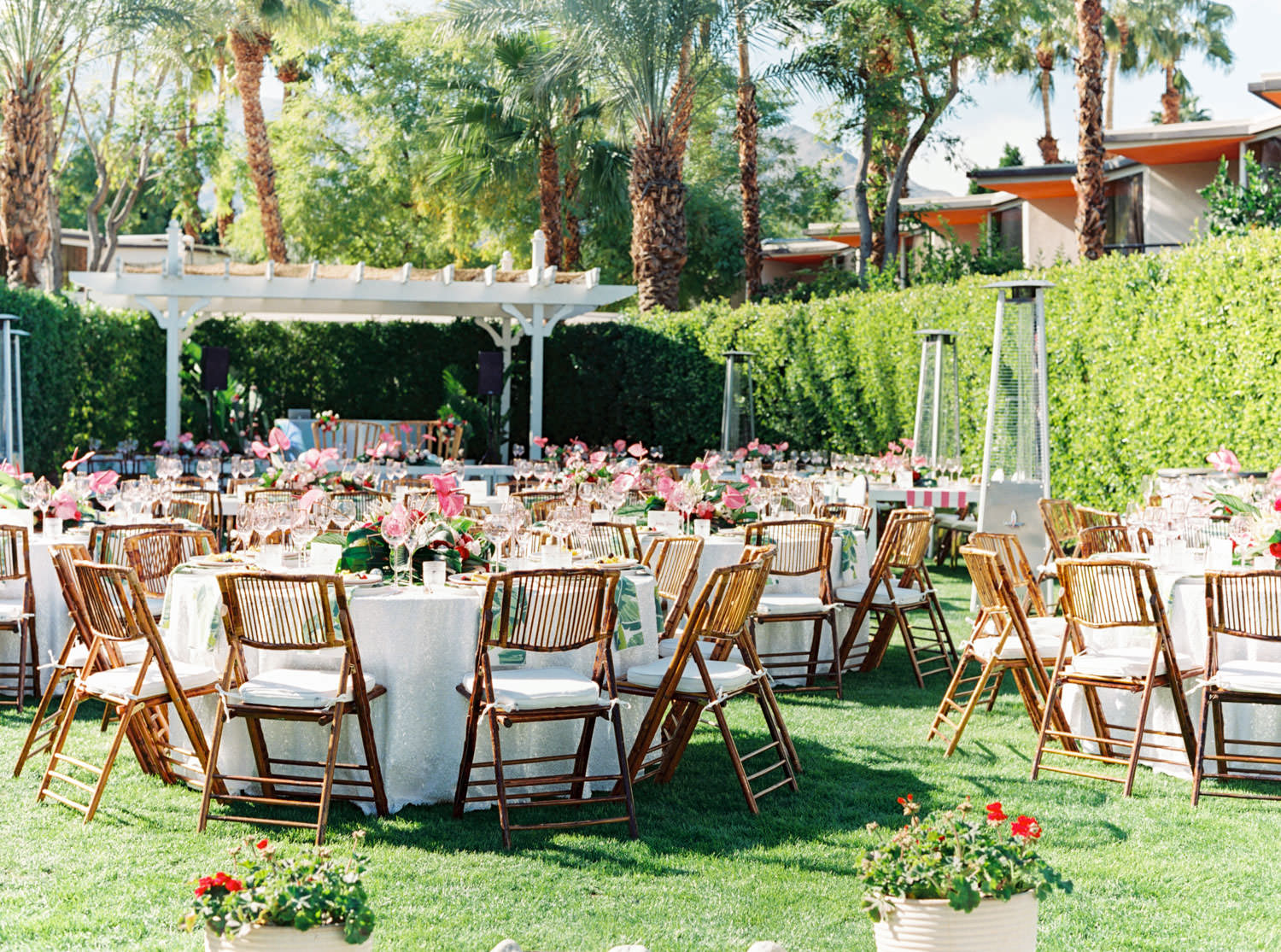 Outdoor brunch reception with round tables covered in sequin linens, bamboo folding chairs with white cushions, and tropical centerpieces with palm leaves, pink anthurium, and proteas. Riviera Palm Springs Wedding by Cavin Elizabeth Photography