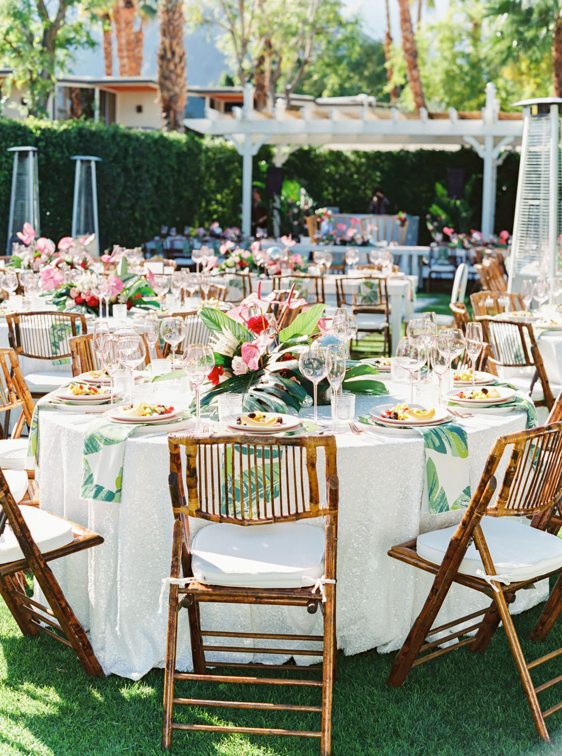 Outdoor brunch reception with round tables covered in sequin linens and palm leaf print napkins, bamboo folding chairs with white cushions, and tropical centerpieces with palm leaves, pink anthurium, and proteas. Riviera Palm Springs Wedding by Cavin Elizabeth Photography