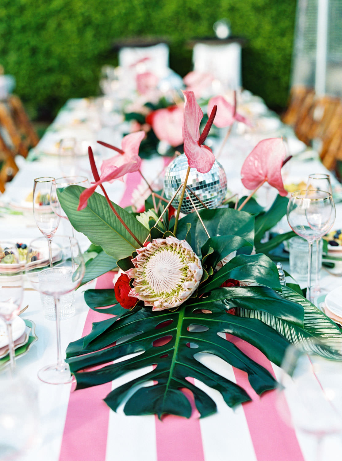 Outdoor brunch reception with long tables covered in pink and white stripe cabana runner, bamboo folding chairs with white cushions, and tropical centerpieces with palm leaves, pink anthurium, and proteas. Riviera Palm Springs Wedding by Cavin Elizabeth Photography