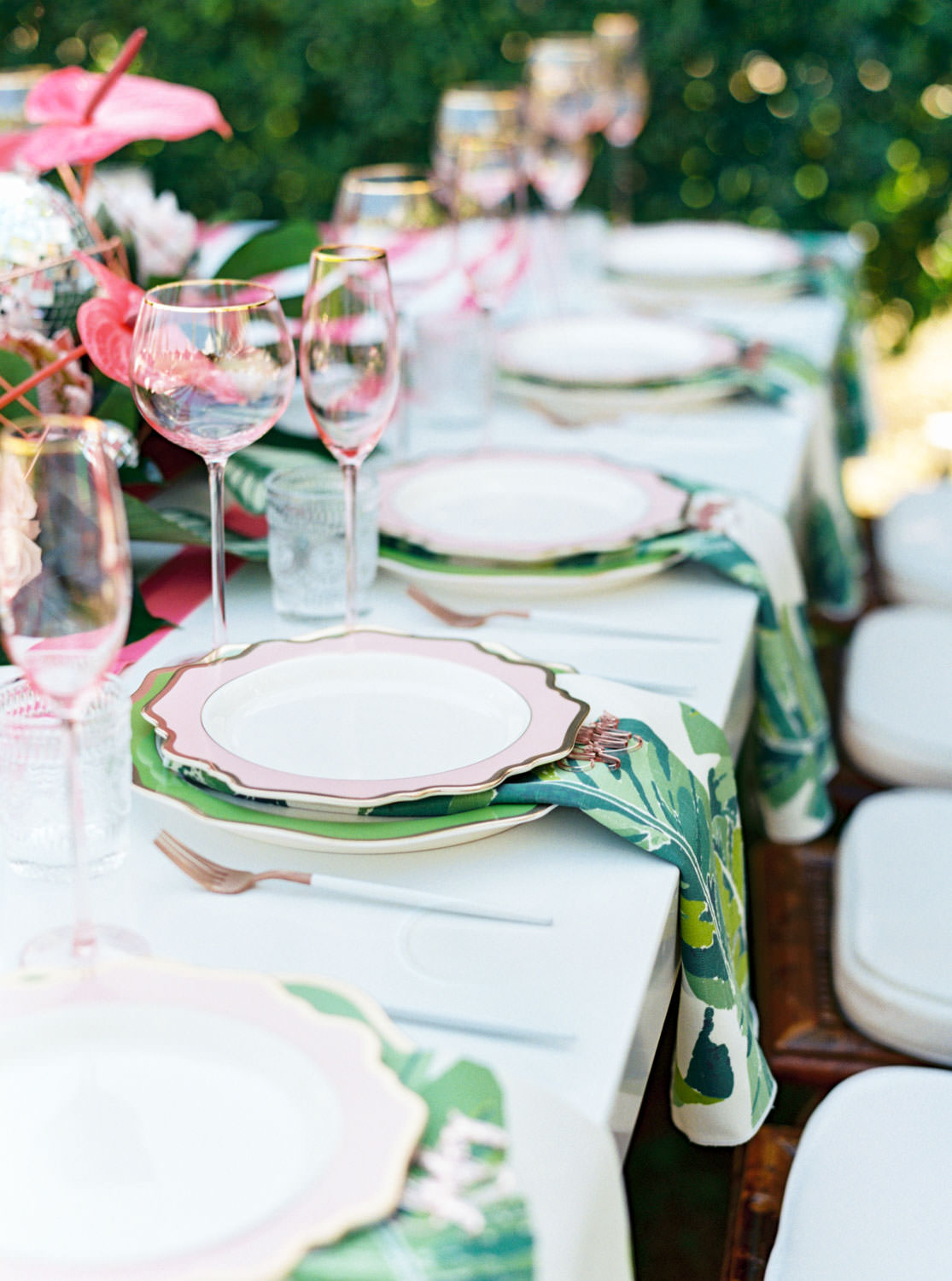 Outdoor brunch reception with long white table, blush and white dinner plate on top of tropical palm leaf print napkin, and tropical centerpieces with palm leaves, pink anthurium, and proteas. Riviera Palm Springs Wedding by Cavin Elizabeth Photography