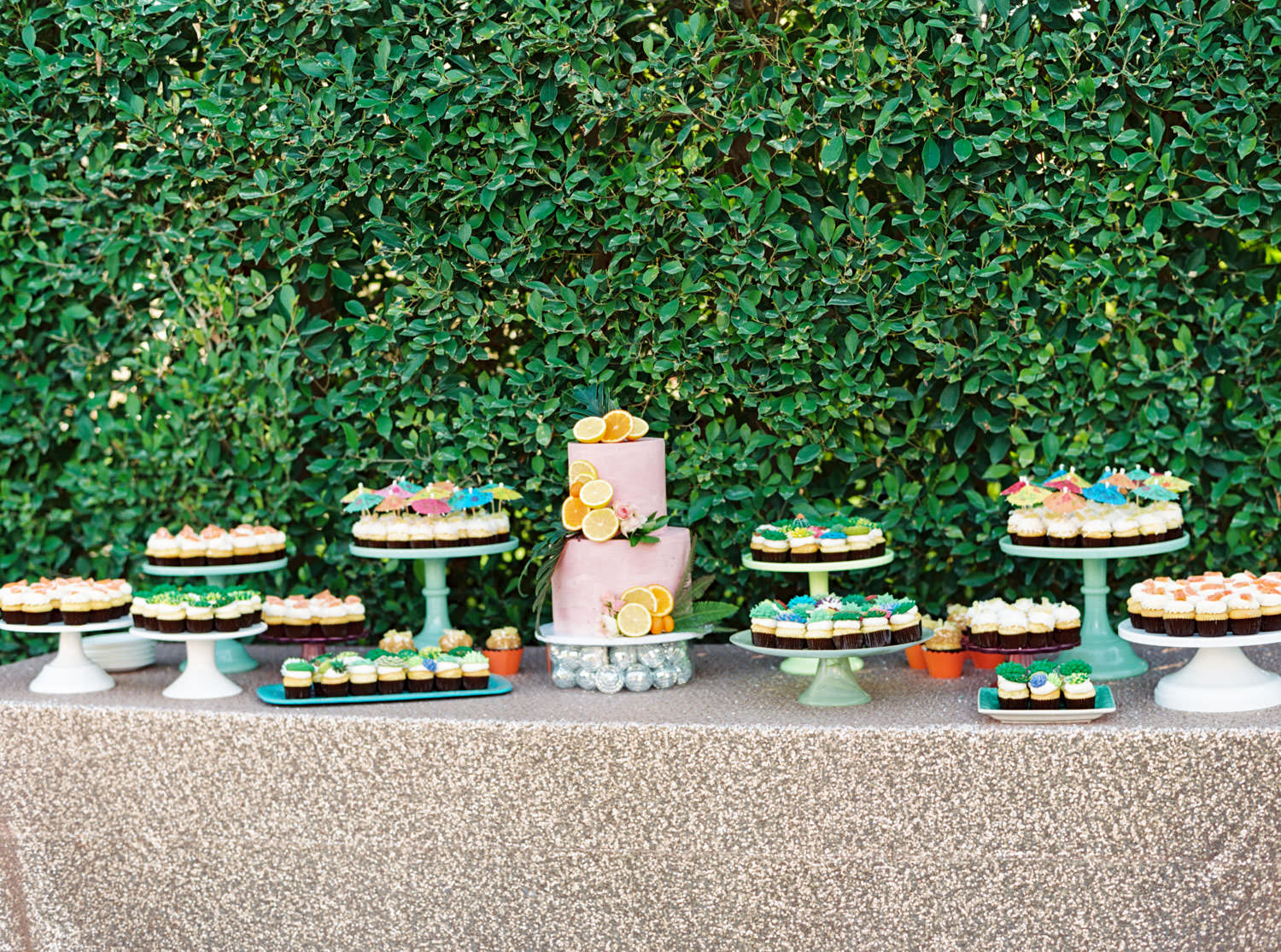 Dessert table with rose gold sequin linen. Tropical desert inspired desserts with succulent icing cupcakes, cocktail umbrella toppers, and a two tier pink cake covered in cut orange and lemon slices and greenery.. Riviera Palm Springs Wedding by Cavin Elizabeth Photography