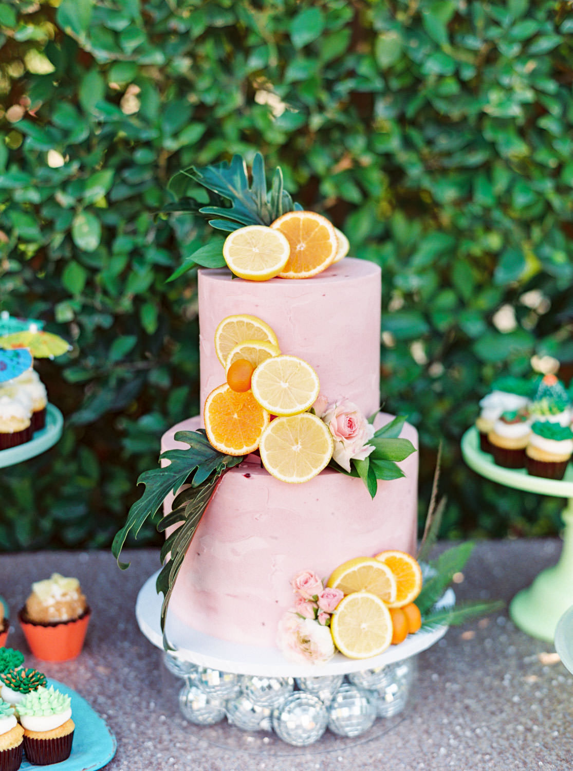 Tropical desert inspired desserts with succulent icing cupcakes, cocktail umbrella toppers, and a two tier pink cake covered in cut orange and lemon slices and greenery.. Riviera Palm Springs Wedding by Cavin Elizabeth Photography