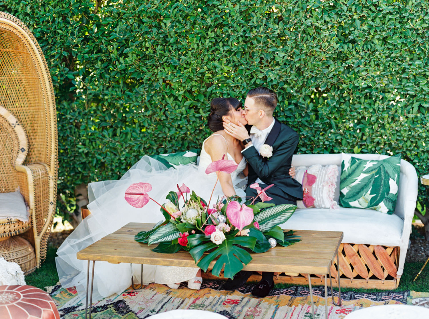 Couple kissing in tropical wedding lounge with boho vibes. White sofa and white tuft seating and palm leaf arrangement on wooden table. Riviera Palm Springs Wedding by Cavin Elizabeth Photography