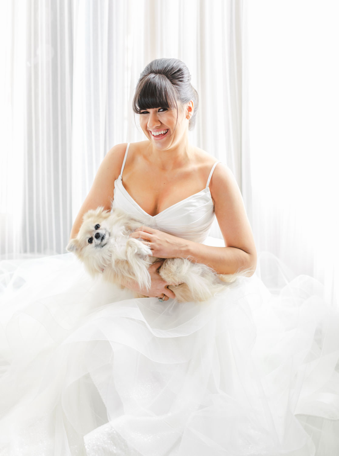 Bride with beehive updo and bangs wearing a Matthew Christopher gown sitting on the floor with her gown spread out and holding her Pomeranian. Cavin Elizabeth Photography