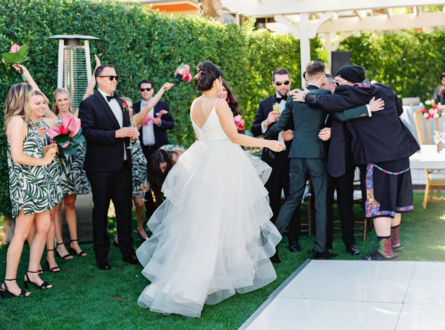 Bride with beehive updo and sleeveless silk gown with layers of tulle for her skirt entering the reception with the groom. Riviera Palm Springs Wedding by Cavin Elizabeth Photography