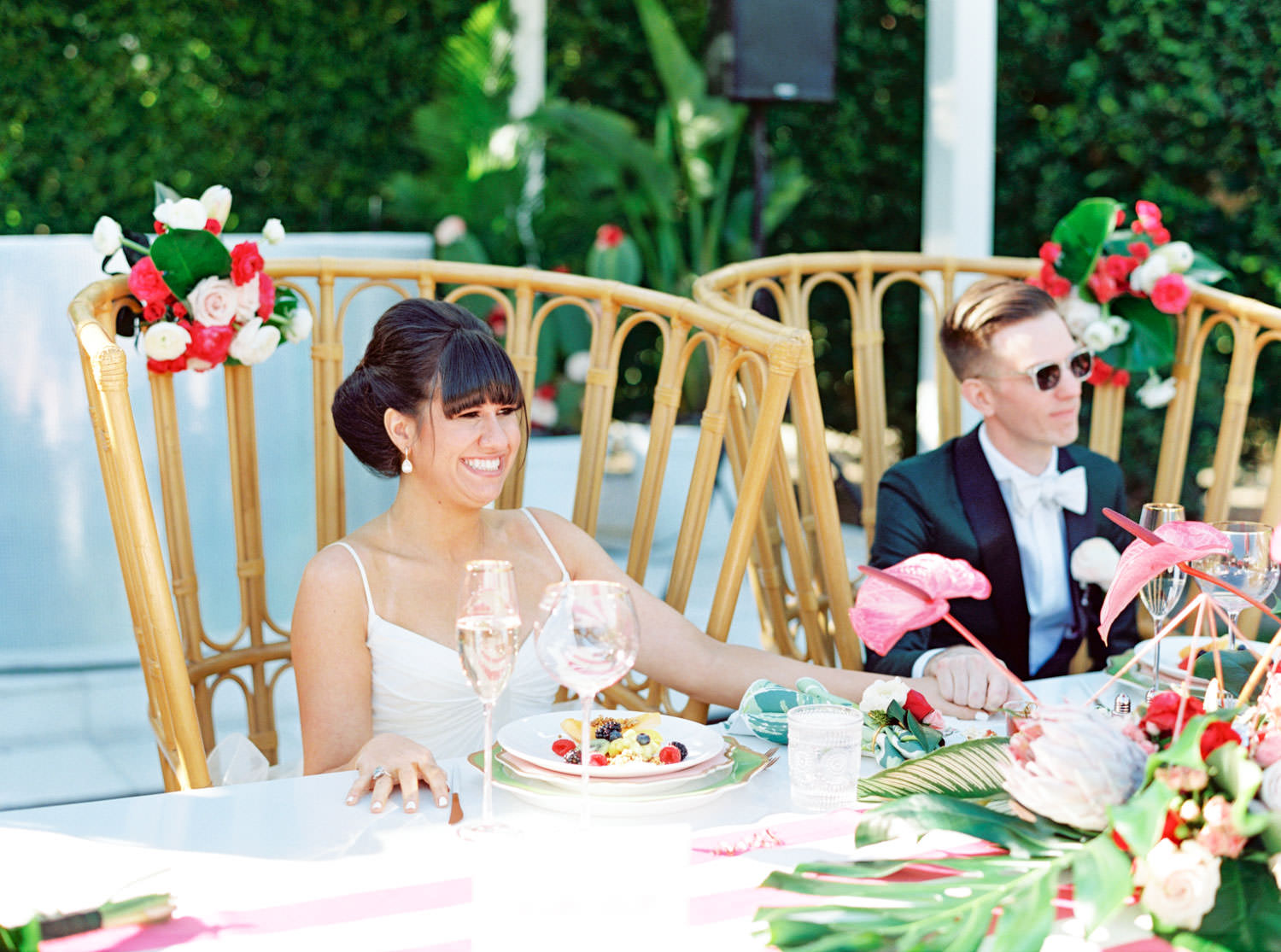 Bride and groom sitting at wedding head table in a large wooden boho chair listening to toasts. tropical centerpieces with palm leaves, pink anthurium, and proteas. Riviera Palm Springs Wedding by Cavin Elizabeth Photography