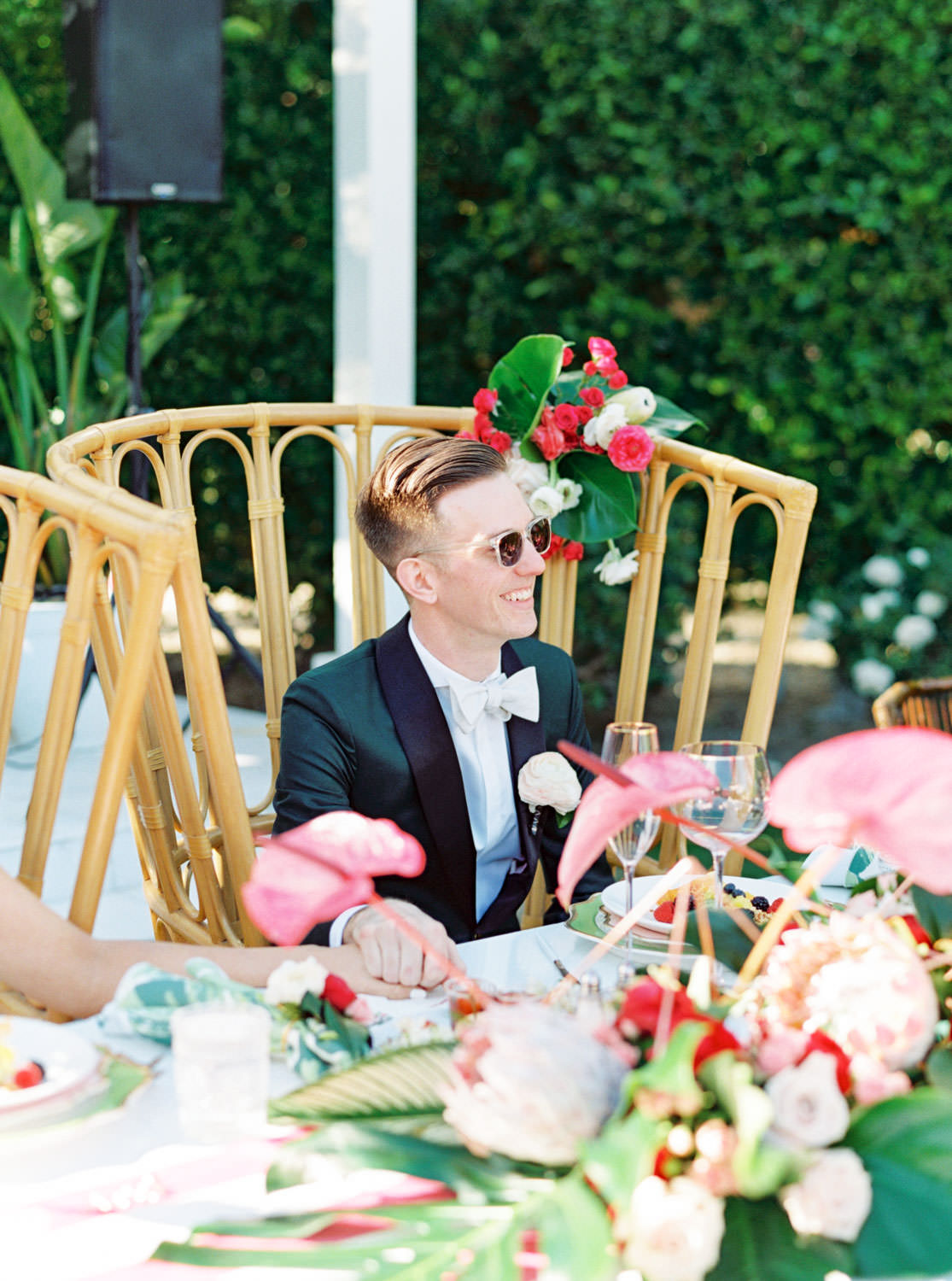 Groom sitting at wedding head table in a large wooden boho chair. tropical centerpieces with palm leaves, pink anthurium, and proteas. Riviera Palm Springs Wedding by Cavin Elizabeth Photography