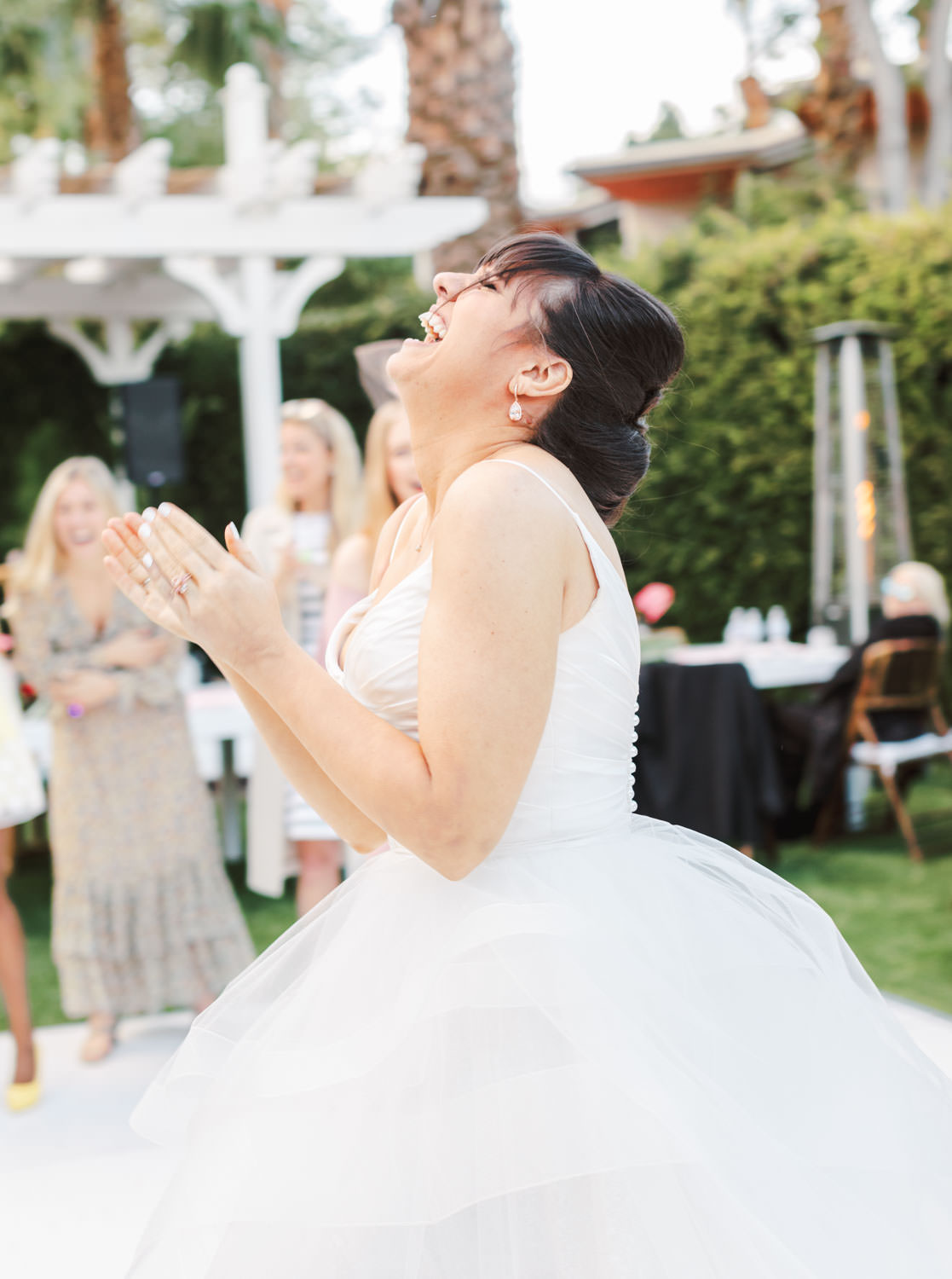 Bride laughing after tossing her bouquet. Riviera Palm Springs Wedding by Cavin Elizabeth Photography