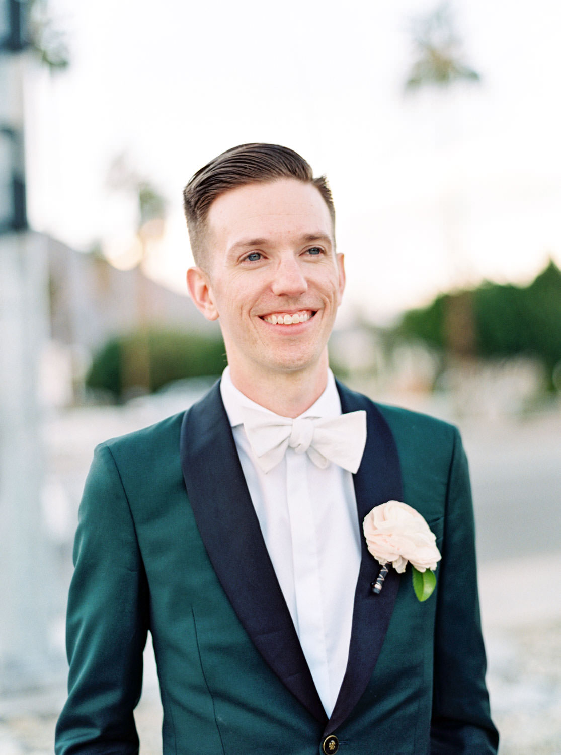 Groom in dark teal tuxedo with large ivory boutonniere and ivory bowtie. Riviera Palm Springs Wedding by Cavin Elizabeth Photography
