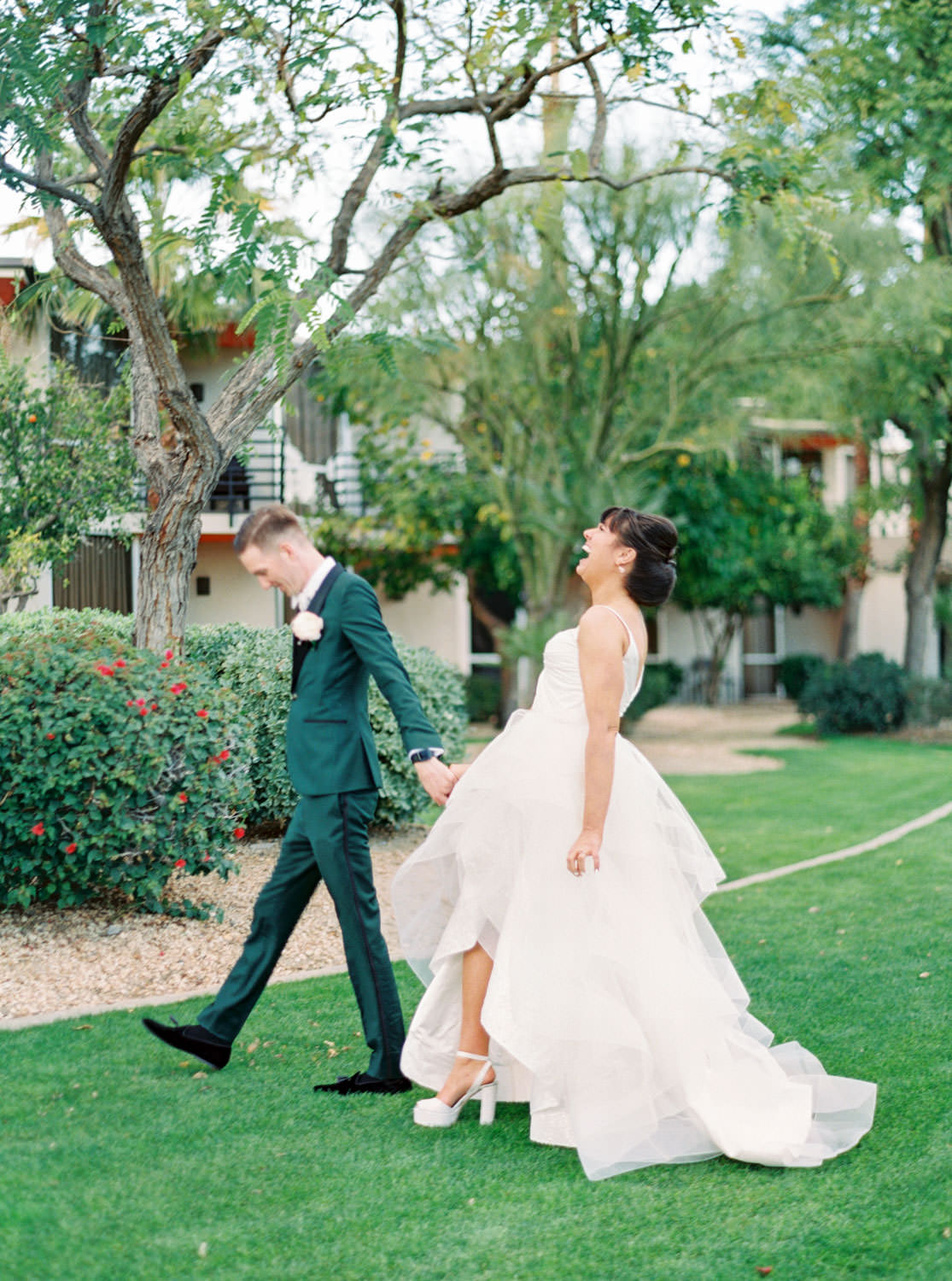 Groom in dark teal tuxedo and bride in beehive updo wearing a Matthew Christopher wedding gown. Riviera Palm Springs Wedding by Cavin Elizabeth Photography