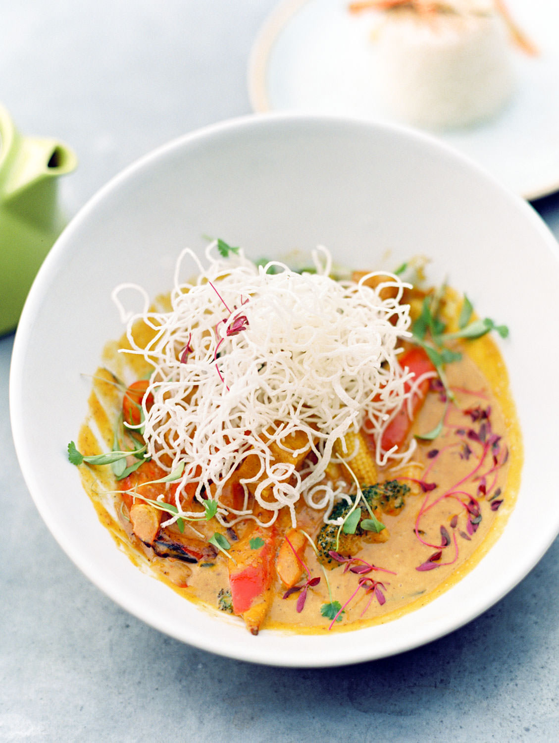 Vietnamese Coconut Curry Bowl Served with fresh vegetables, tofu, jasmine rice and pickled vegetable salad. Garnished with holy basil and crispy noodles from The Green Rocket in Bath England, Cavin Elizabeth Photography