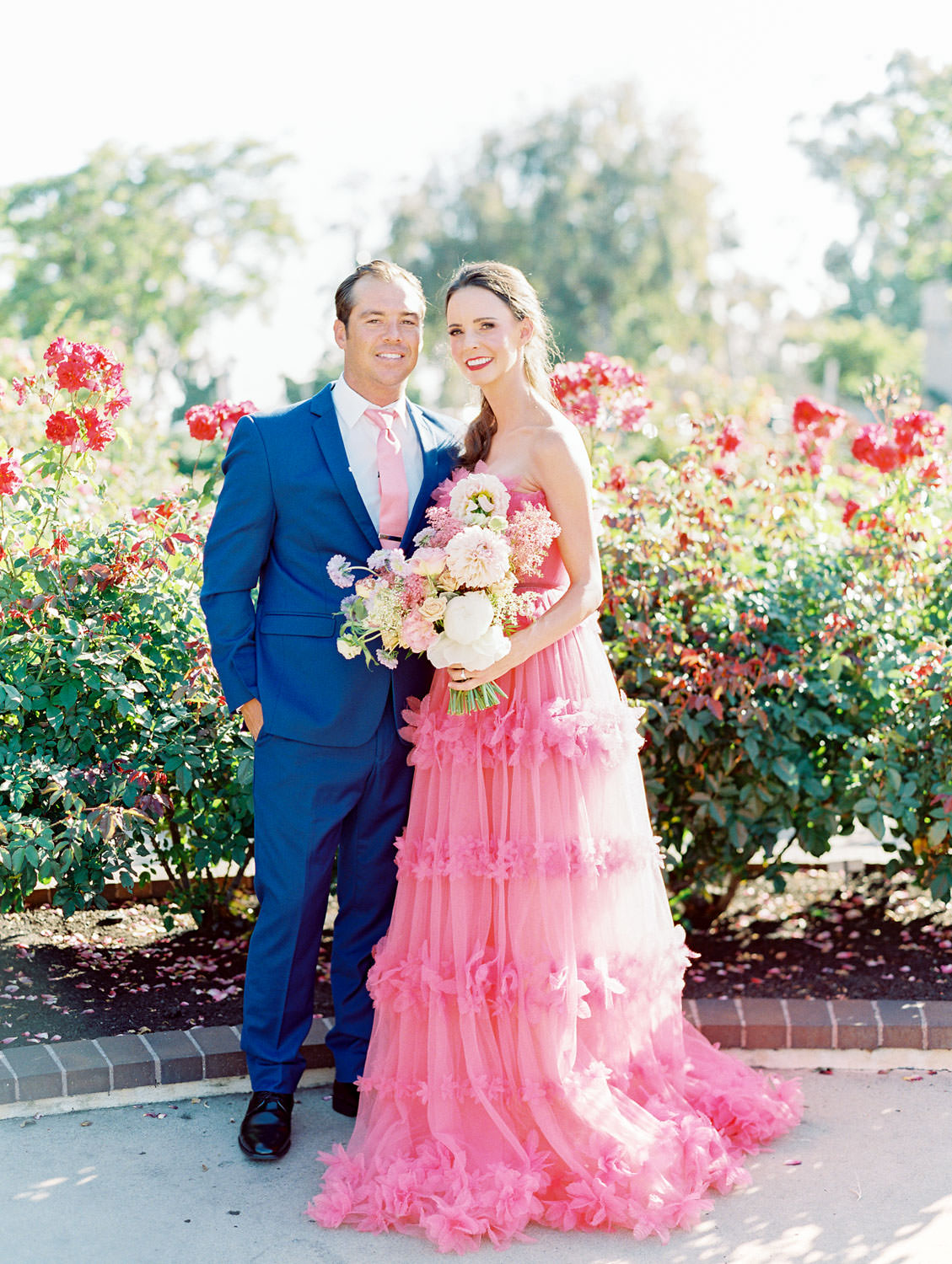 Bride in pink strapless Marchesa Notte gown holding bouquet with pink, lavender, ivory, and green flowers in a rose garden. Groom in blue suit and pink tie to match his wife. Balboa Park San Diego Anniversary Photos by Cavin Elizabeth Photography