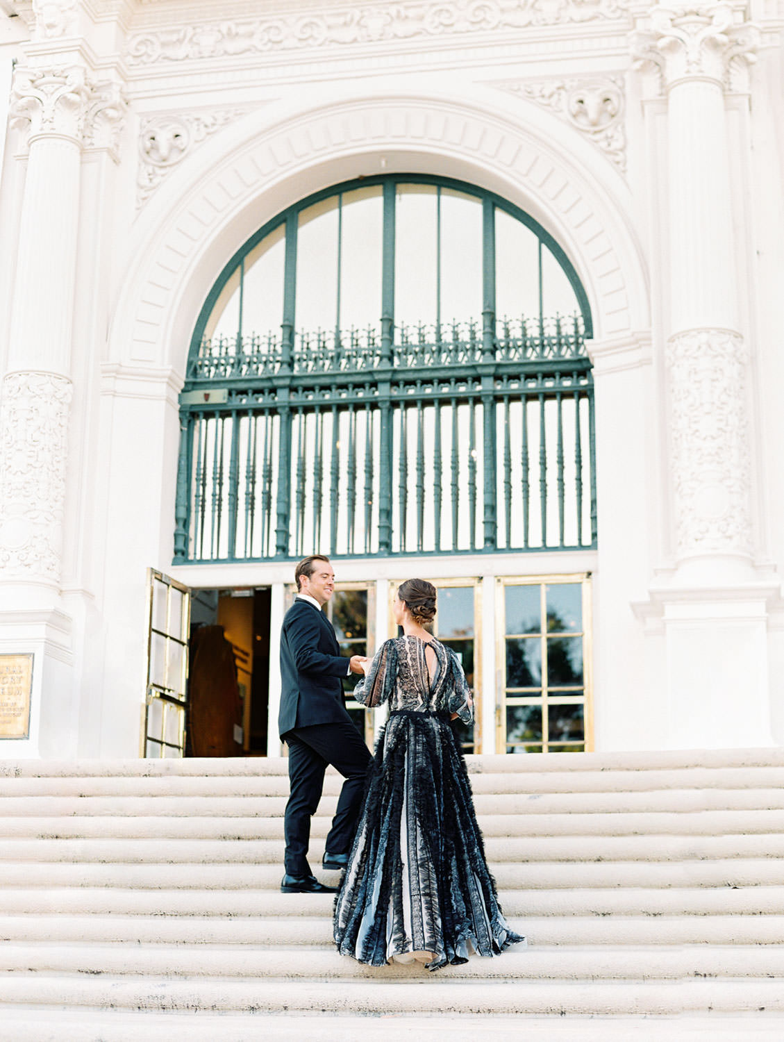 Bride in a black long sleeve lace Marchesa couture gown and groom in a black suit and tie to match his wife. Walking up the stairs of a beautiful building. San Diego Anniversary Photos in Balboa Park on film by Cavin Elizabeth Photography