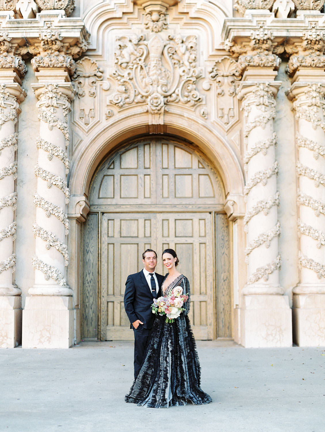 Bride in a black long sleeve lace Marchesa couture gown holding a pink, ivory, and green bouquet. Groom in a black suit and tie to match his wife in front of the Casa Del Prado Theatre. San Diego Anniversary Photos in Balboa Park on film by Cavin Elizabeth Photography