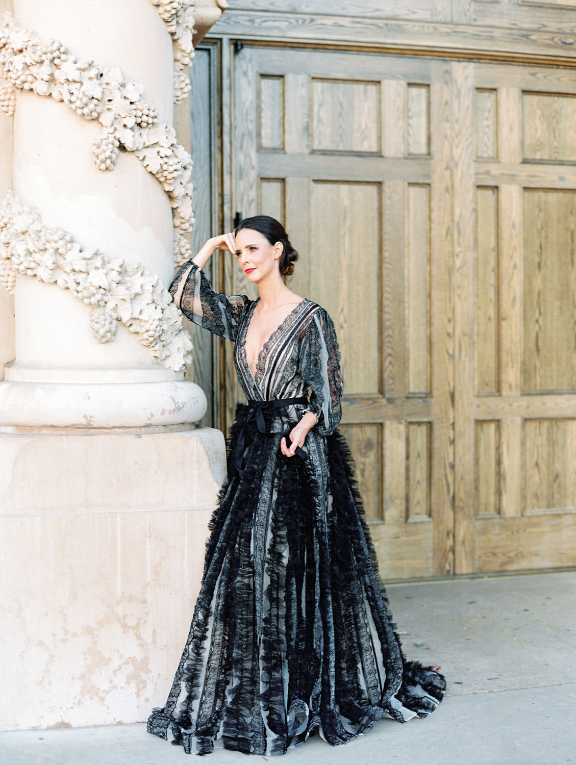 Bride in a black long sleeve lace Marchesa couture gown in front of the Casa Del Prado Theatre. San Diego Anniversary Photos in Balboa Park on film by Cavin Elizabeth Photography