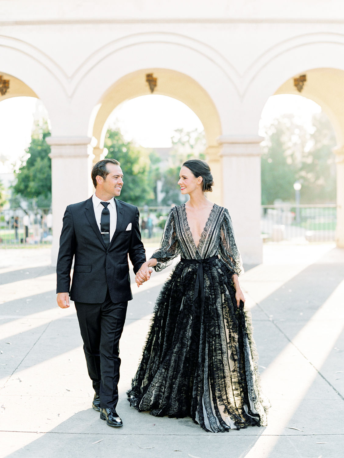 Bride in a black long sleeve lace Marchesa couture gown. Groom in a black suit and tie. Couple walking together with dreamy lighting. San Diego Anniversary Photos in Balboa Park on film by Cavin Elizabeth Photography