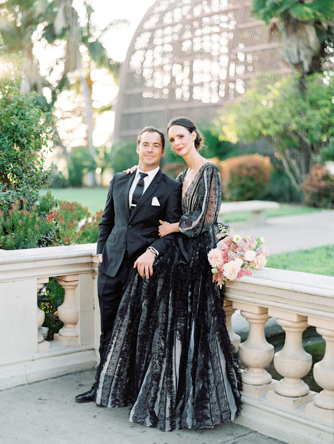 Bride in a black long sleeve lace Marchesa couture gown with a pink, ivory, and green bouquet. Groom in a black suit and tie to match his wife in front of the Casa Del Prado Theatre. San Diego Anniversary Photos in Balboa Park on film by Cavin Elizabeth Photography