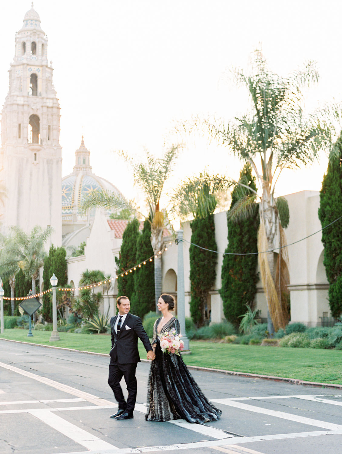 Bride in a black long sleeve lace Marchesa couture gown holding a pink, ivory, and green bouquet. Groom in a black suit and tie to match his wife in front of the bell tower. San Diego Anniversary Photos in Balboa Park on film by Cavin Elizabeth Photography