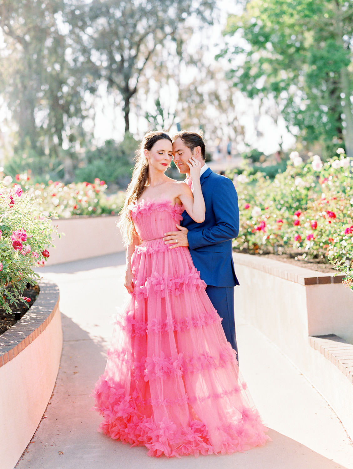 Bride in pink strapless Marchesa Notte gown in a rose garden. Groom in blue suit and pink tie to match his wife. Balboa Park San Diego Anniversary Photos by Cavin Elizabeth Photography